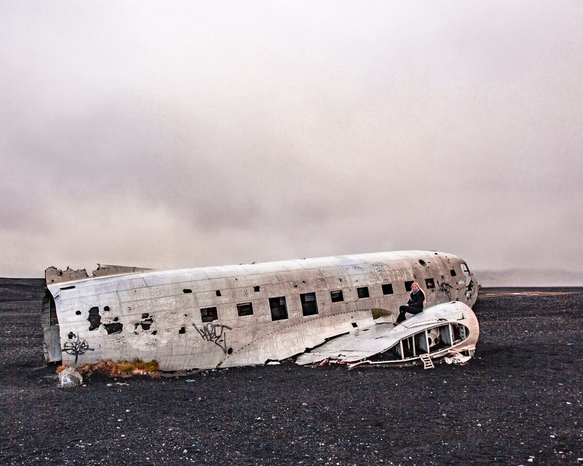 A woman sitting on the famous Iceland airplane crash