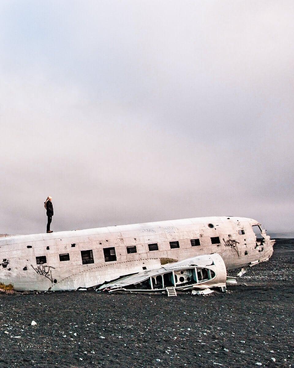 A woman on top of the Sólheimasandur plane crash