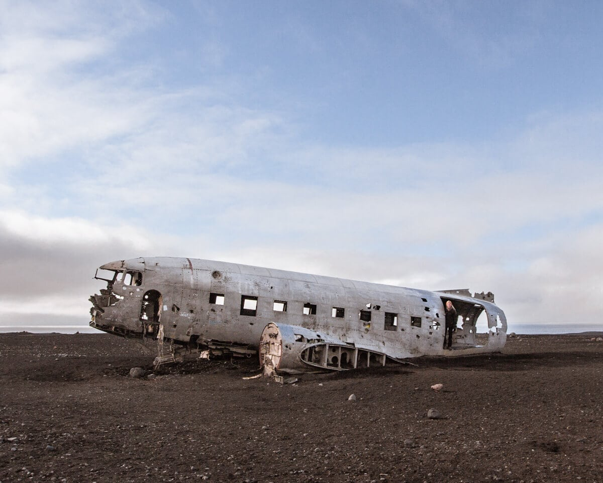 A woman standing in the doorway of the Sólheimasandur plane crash in Iceland