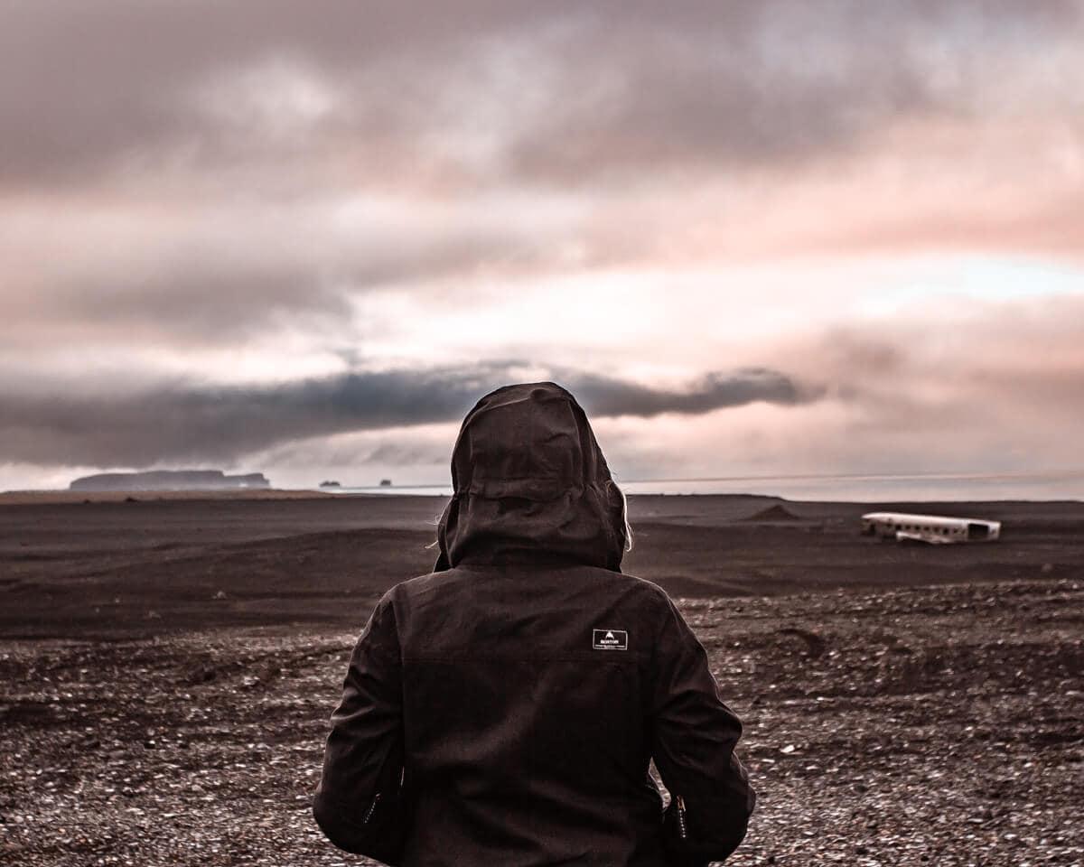 A woman looking out at Dyrhólaey and the Sólheimasandur plane wreck